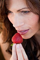 Brunette woman holding a strawberry to her lips