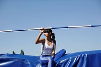 Woman sitting on a high jump safety mat