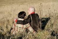 Mature couple sitting on grass