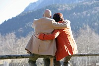 Mature couple sitting on a fence and embracing