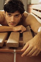 Darkhaired Man lying procumbently on a wooden Bench - Look - Allurement (thumbnail)