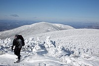 Winter hiker on the summit of South Twin Mountain during the winter months in the White Mountains, New Hampshire USA