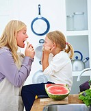 Young mother with her daughter in kitchen eating watermelon