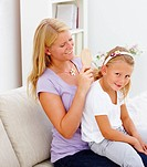 Young mother sitting on sofa and combing her daughter´s hair