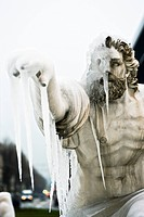 Statue of fierce male figure pointing to distance, face obscured by icicles