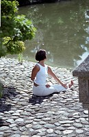 Darkhaired Woman doing physical Exercise at the Shore of a Lake - Yoga - Harmony - Nature (thumbnail)