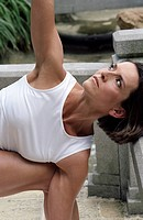 Darkhaired Woman stretching her Arm up _ Physical Exercise _ Yoga _ Terrace