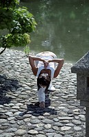 Darkhaired Woman doing physical Exercise at the Shore of a Lake _ Yoga _ Harmony _ Nature