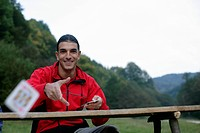 Young man with black hair is throwing a card, selective focus (thumbnail)