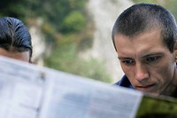 Two men looking at a magazine part of, close_up