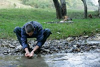 Brunette man is washing his hands at the shore of a rivulet