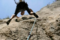 Man climbing up a rock face, low angle view