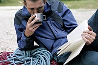 Young man with ropes lying next to him on the ground is reading a book and drinking from a metallic cup part of, selective focus