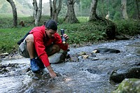 Young man with black hair is illuminating a spot of a rivulet with a flashlight