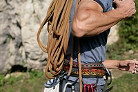 Young muscular man carrying a very long rope on his shoulder, selective focus