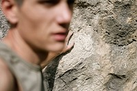 Young man in front of a rock face, selective focus