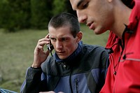 Young man is phoning with a mobile while standing next to another man