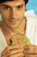 Darkhaired Man in a Bathrobe holding a Sandwich in his Hands _ Snack _ Foodstuff _ Look