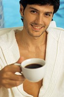 Darkhaired Man in a Bathrobe holding a Cup of Coffee in his Hand _ Look _ Hot Beverage _ Leisure Time