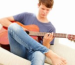 Teenage boy sitting on a sofa and playing the guitar