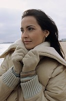Young darkhaired Woman cuddling herself into the Collar of her winterly Jacket _ Season _ Gesture _ Beach