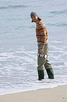 Young redhaired Man with woolen Hat and Wellies in the Water _ Fun _ Beach