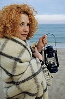 Young redhaired Woman holding an Oillamp _ Twilight _ Atmosphere _ Beach