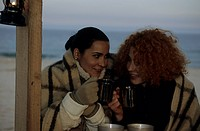 Two female friends with Cups under one Blanket _ Coldness _ Friendship _ Beach _ Season