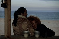 Redhaired Woman leaning against a Friend _ Coldness _ Friendship _ Beach _ Season
