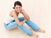 Closeup of a happy young lady sitting on floor looking up
