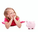 Small baby looking at piggy bank against white background