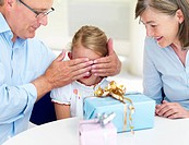 Closeup of a happy grandparents closing eyes of their granddaughter with gifts on table
