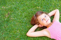 Top view of a sweet little girl relaxing on the grass