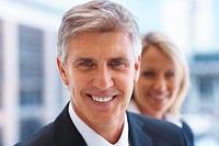 Closeup portrait of a business man with an associate in the background