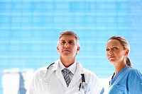 A team of attractive doctors in uniform looking away on a bluish background