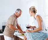 Mature man preparing salad while his wife is having wine