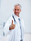Blurred image of a senior doctor showing a thumbs up sign