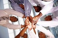 Team of business colleagues with their hands together in unity