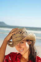 Attractive young female posing in a cowboys hat by the sea