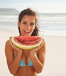 A sexy hot lady smiling with a big piece of watermelon