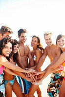 Cheerful friends at the beach with their hands together