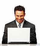 A Happy successful business man smiling while working on laptop