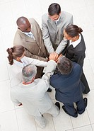 Upward view of business people standing in a circle with their hands together