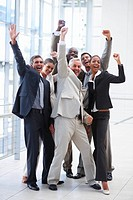 Full length portrait of successful delighted business people with their hands raised
