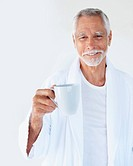 An aged cheerful handsome old man holding a cup of coffee and smiling