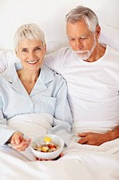 Cute old couple in bed having a bowl of fresh fruits