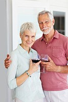 Portrait of an elderly couple celebrating with a glass of wine