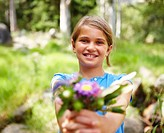 Portrait of a cute young girl offering a bouquet of flowers