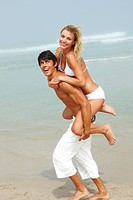 Young handsome male carrying female piggyback style on the beach