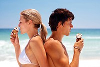 Couple at the beach eating ice cream and smiling